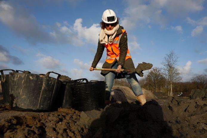 Ontwerper Iris Veentjer schept in de bouwput van rijksweg A16 Rotterdam bij de Rotte zeven emmers vol met klei, waarvan ze haar nieuwe Rottekoppen gaat maken.
