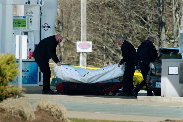 Medewerkers van de politie dragen een lichaam weg bij een benzinestation in Enfield in de Canadese provincie Nova Scotia. Vermoedelijk gaat het om de schutter die afgelopen weekeinde zeker 18 mensen doodschoot voordat hijzelf door de politie werd gedood. Beeld null