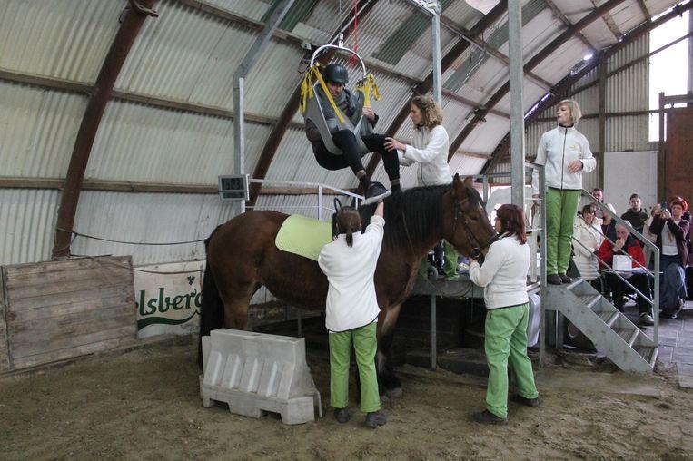 Via een platform en een special lift wordt de patiënt op het paard getild.