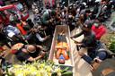 Mensen maken foto's van een Indonesiër die door een minuut in de kist te gaan liggen zijn coronaboete niet hoeft te betalen.