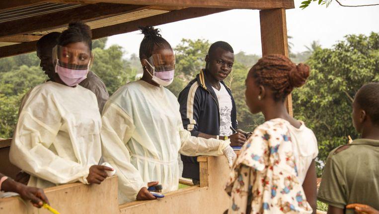 Ebolahulpverleners controleren reizigers bij de grensovergang met Liberia. Beeld afp