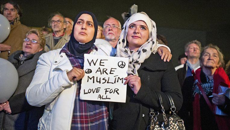 Twee Moslimvrouwen betuigen hun solidaritiet met de slachtoffers van de aanslagen in Parijs tijdens een herdenkingsbijeenkomst in Rotterdam. Beeld Guus Dubbelman / de Volkskrant