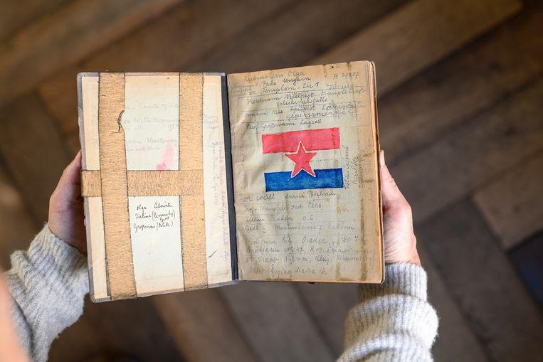 Melcher de Wind met het schrift waarin zijn vader in Auschwitz zijn verhaal opschreef. Het was een schrift waarin de SS de administratie van de gevangenen bijhield. De afbeelding is een combinatie van de Nederlandse vlag met de ster van het Rode leger. Eddy was als arts in dienst gekomen in het Rode Leger. Beeld Els Zweerink