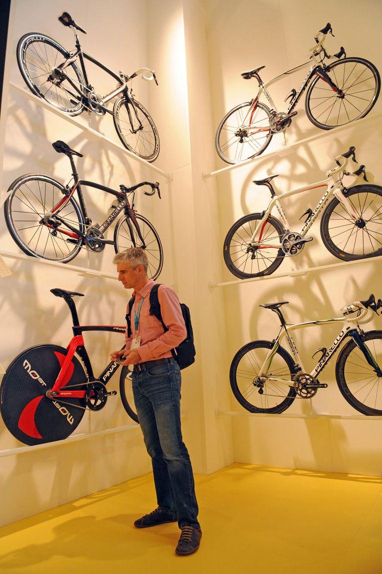Kijken, kijken, niet kopen. Een bezoeker op een fietsbeurs vergaapt zich aan Pinarello's. Beeld afp