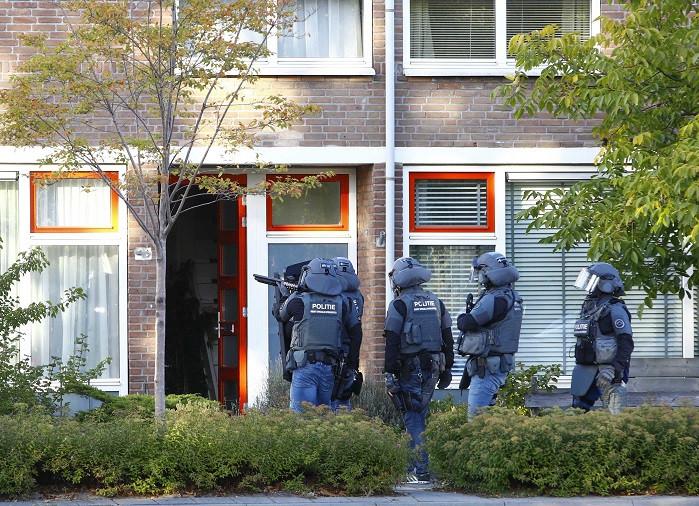 Met getrokken wapens gaan medewerkers van het arrestatieteam van de politie de woning binnen.