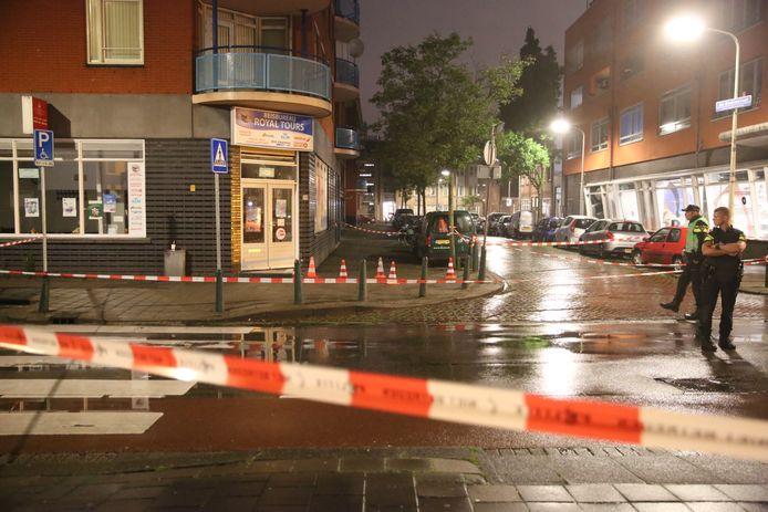 In de deuren van het reisbureau aan de Hoefkade zijn kogelgaten te zien. De politie zette de straat af en doet onderzoek.
