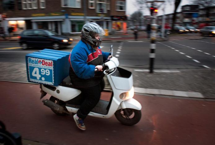 Een pizzakoerier op een elektrische scooter.