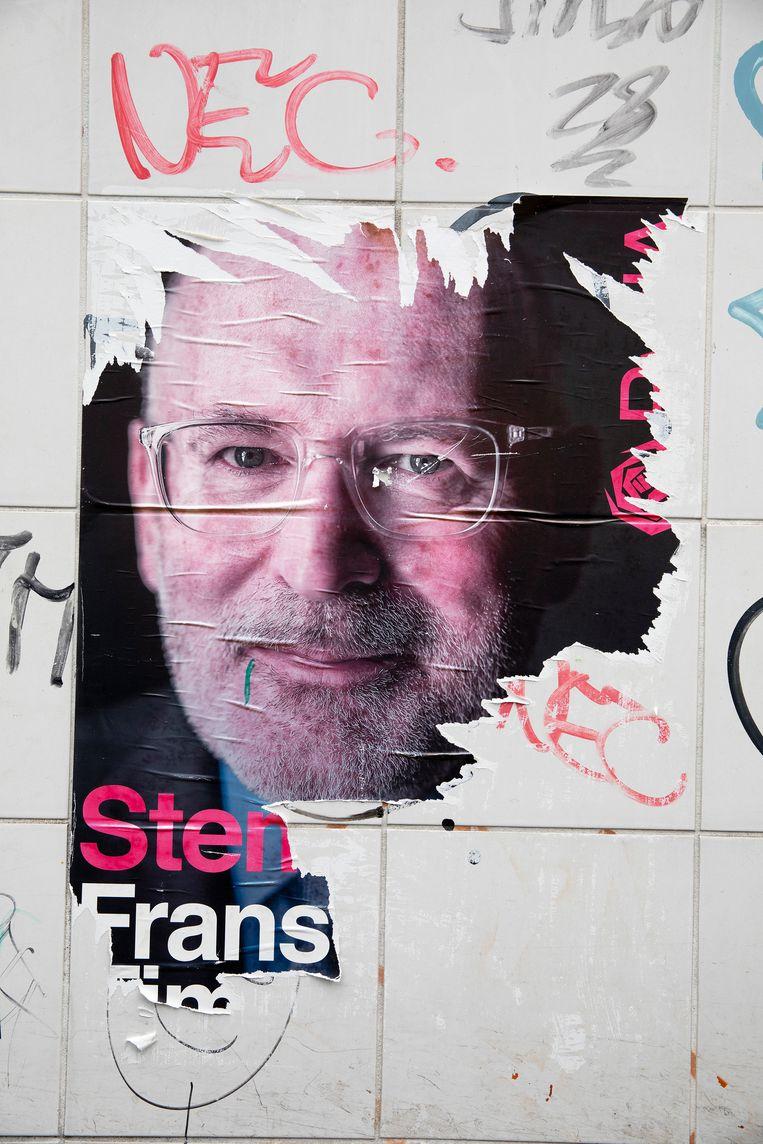 Restanten van een poster met het portret van politicus Frans Timmermans aan een muur in het centrum van Nijmegen. Beeld Theo Audenaard