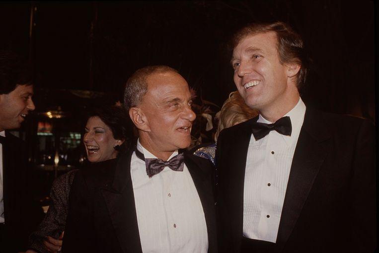1983: Roy Cohn (links) en Donald Trump bij de opening van de Trump Tower in New York. Beeld Getty