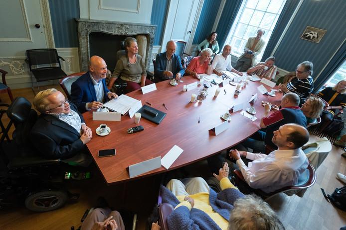 Rick Brink (l.) met om de tafel gisteren wethouder Cees van Eijk en twaalf Amersfoorters met een beperking.