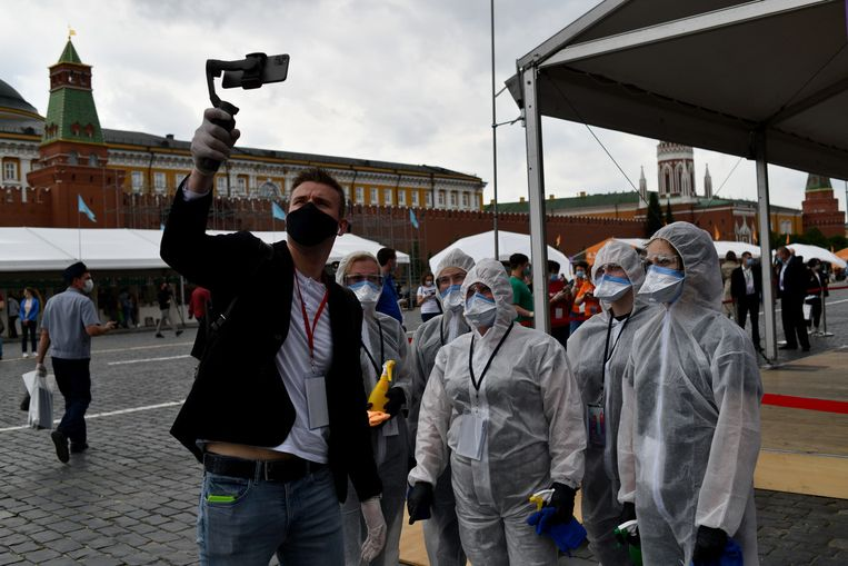 Een blogger maakt een video met ingepakte vrijwilligers met spuitflessen met ontsmettingsmiddel, op de bijna uitgestorven boekenmarkt op het Rode Plein.  Beeld Yuri Kozyrev / Noor