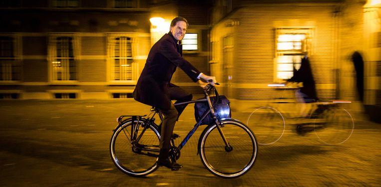 Premier Mark Rutte verlaat het Binnenhof op de fiets. Beeld ANP