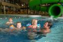 Finn (links), Mees, Liva en papa Harrie Beekhuis ravotten in het water van zwembad De Koekoek in  Vaassen.