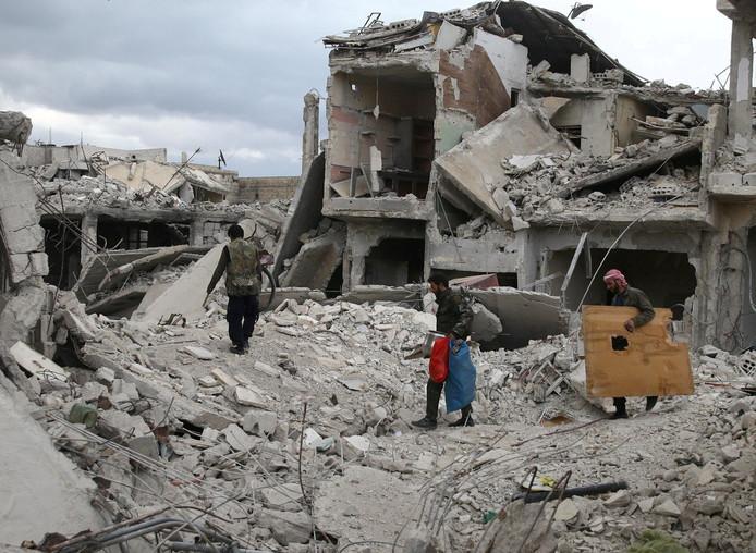 Bewoners lopen langs verwoeste gebouwen in Douma.
