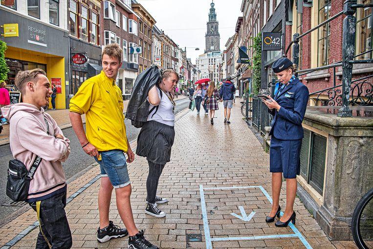 Stewards en stewardessen staan buiten een winkel van hun maatschappij TUI in Groningen om tickets te verkopen.  Beeld Guus Dubbelman / de Volkskrant