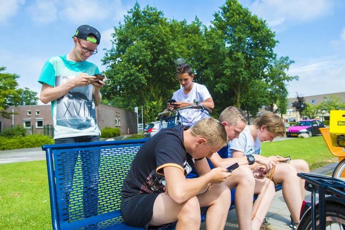Jongeren hangen rond bij de speeltuin van Schuylenburg, op jacht naar pokémon.