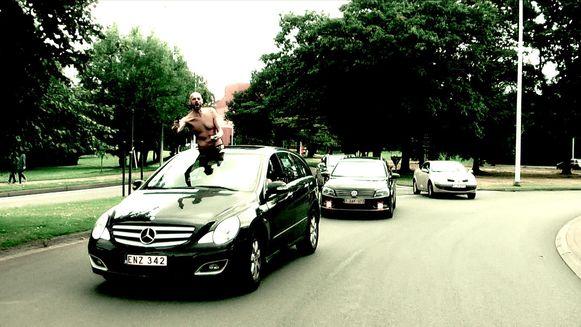 Uit 'Bonnie&Clyde Copycats': een gangster hangt uit het dakraam van een Mercedes op de Unesco-rotonde.
