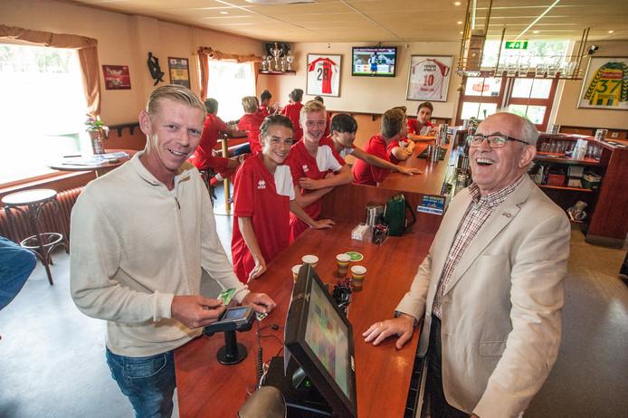 Richard van den Nieuwendijk (links) betaalt cashless zijn drankjes aan Willem Versteeg in de voetbalkantine van de Alphense boys.