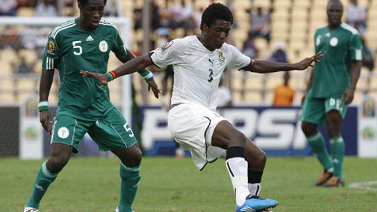 De Ghanese speler Asamoah Gyan (midden) houdt de bal weg van de Nigeriaanse speler Obinna Nwaneri (L). (EPA) Beeld