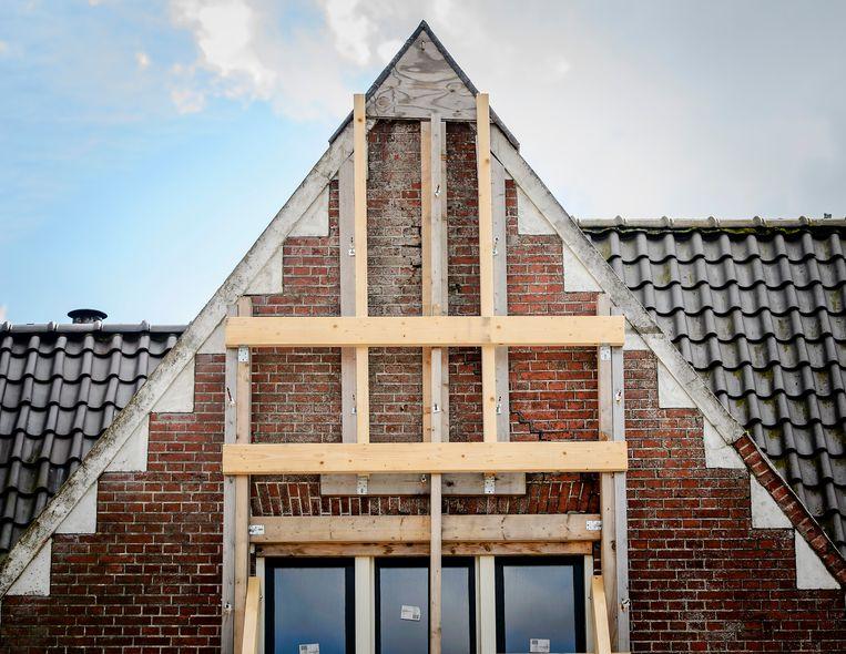 Een gebouw in Zeerijp is verstevigd met balken als gevolg van aardbevingsschade die is ontstaan door de gaswinning van de NAM in het gebied. Beeld ANP