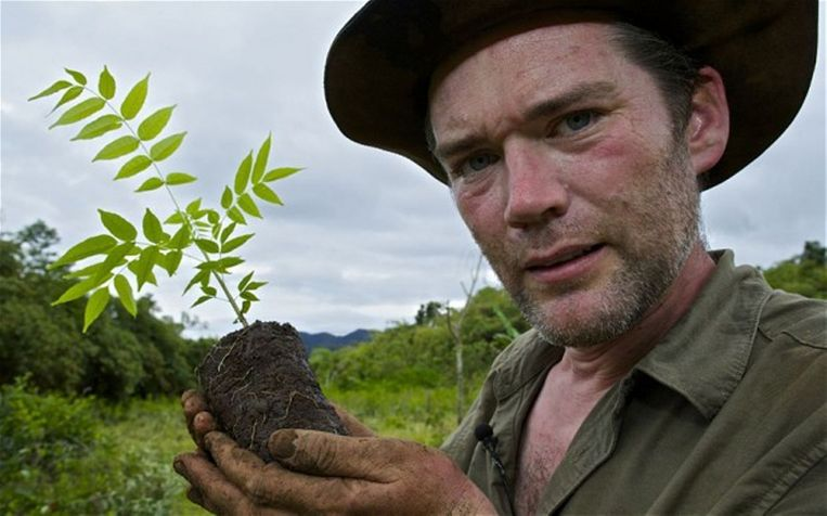 Natuurfotograaf Charlie Hamilton met een plantje voor het door hem gekochte regenwoud in Peru. Beeld BBC