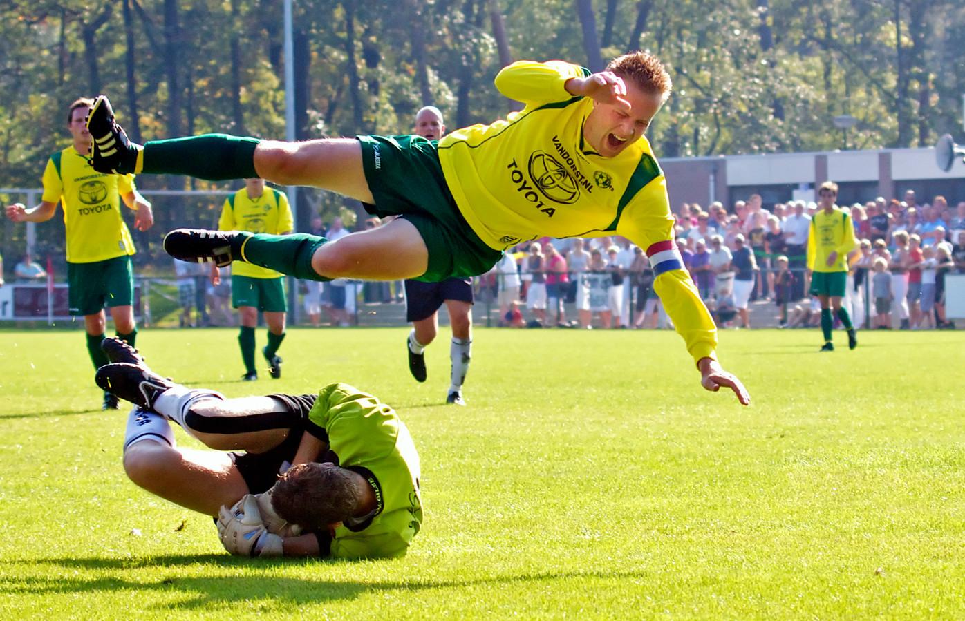 Het gaat er vaak heet aan toe in de derby tussen Gilze en Rijen, zoals hier in oktober 2011. Rijen-aanvoerder Lennart Kessels vliegt door de lucht na een botsing met Gilze-doelman Ralf van Gestel.