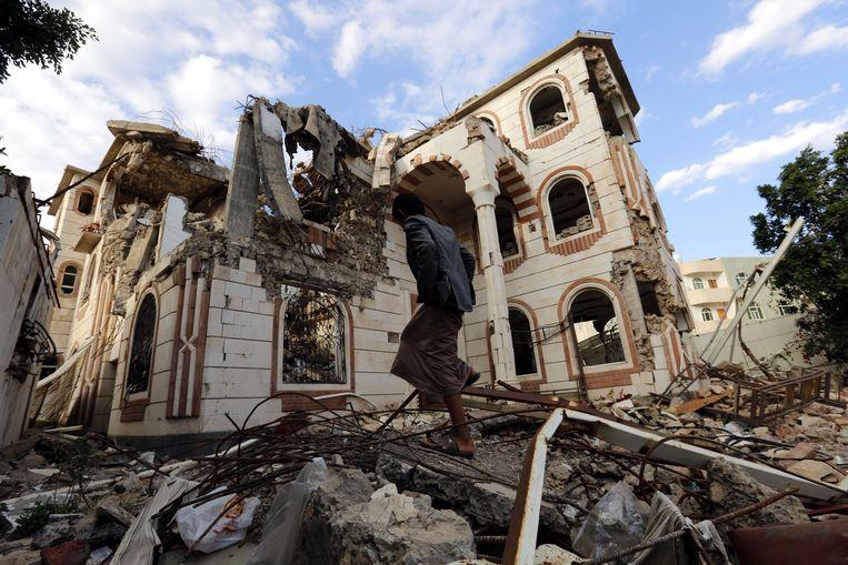 Een Jemeniet loopt door de puinhopen van een verwoest gebouw in Sanaa, na vermoedelijk een Saudisch bombardement. Beeld EPA