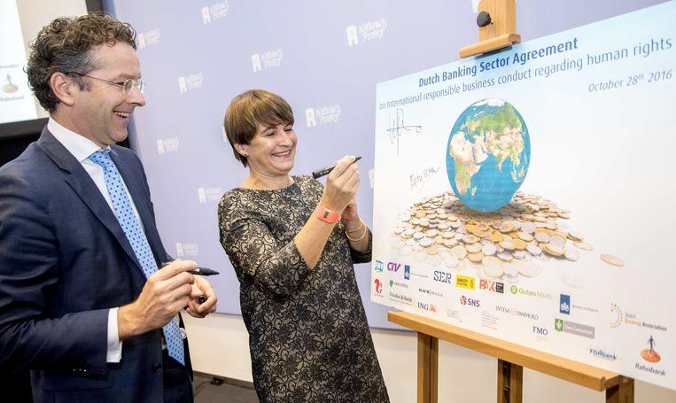 Voormalige ministers Jeroen Dijsselbloem van Financiën en Lilianne Ploumen van Buitenlandse Handel ondertekenen het convenant internationaal maatschappelijk verantwoord ondernemen in de bancaire sector (2016). Beeld ANP