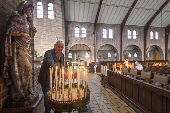 Voorzitter Fons Kox van de locatieraad steekt een kaarsje op in de H. Caeciliakerk in Neede.