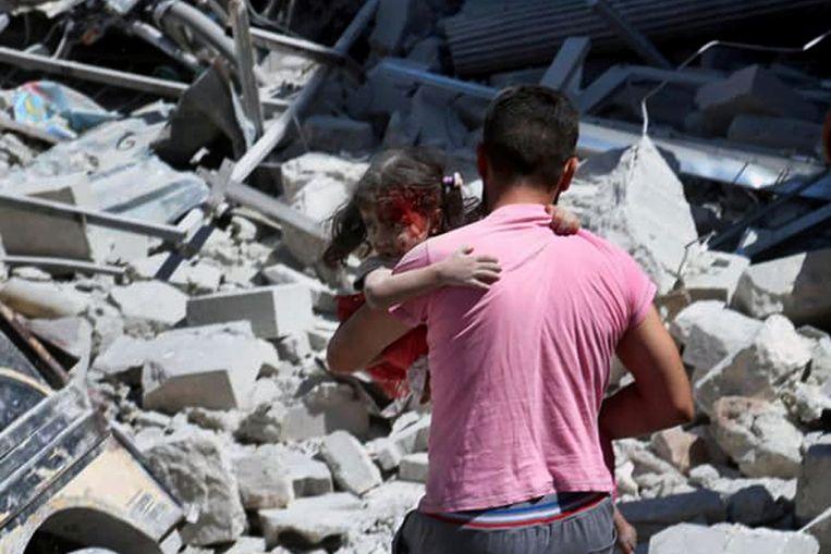 Een Syrische man met een gewond kind na een recente luchtaanval op Ariha, in Idlib.