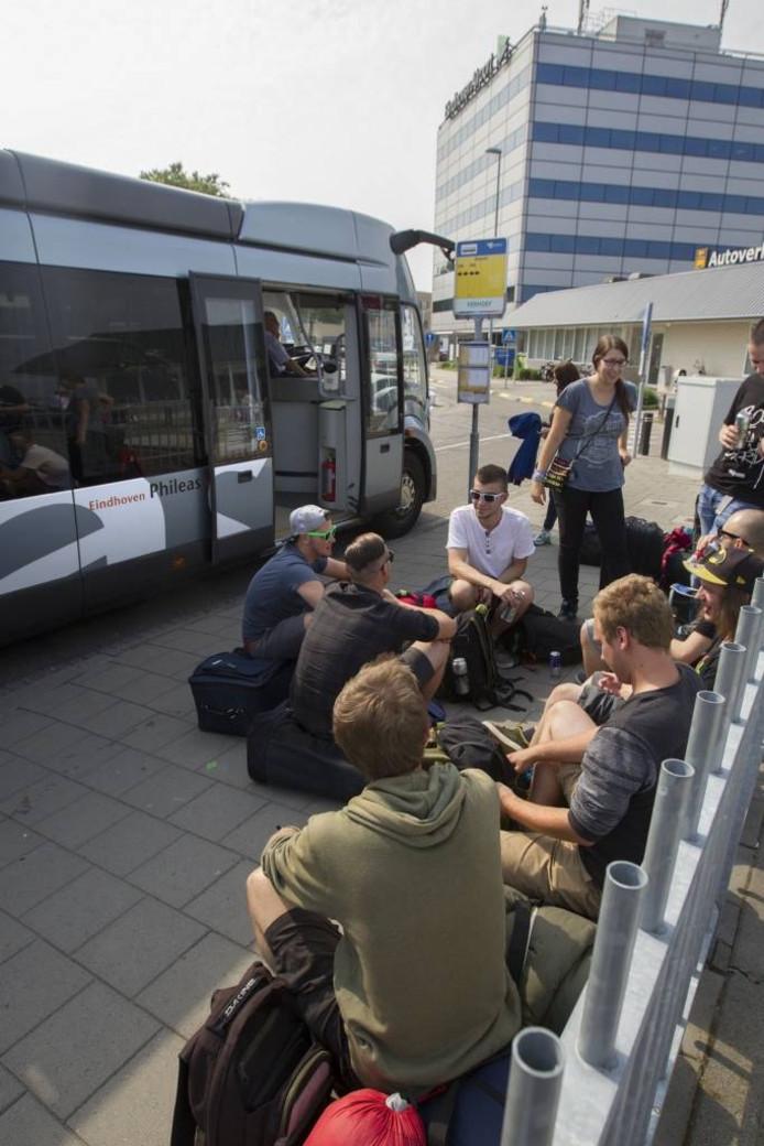 Reizigers wachten bij de bushalte van Eindhoven Airport op verder vervoer. Kees Martens/Fotomeulenhof