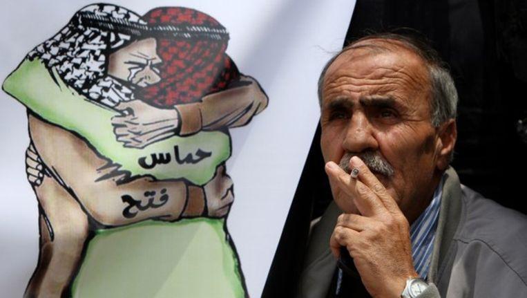 Spotprent in Jeruzalem waarop een aanhanger van Fatah en Hamas elkaar omhelzen. Beeld afp