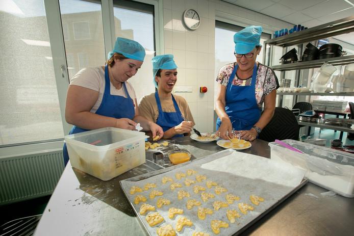 Op de foto strijkt Thomas Blokdijk ei op een koekje, daarbij geholpen door de activiteitenbegeleiders Anouk van Gorp (l) en Marian van Heerenbeek (r).