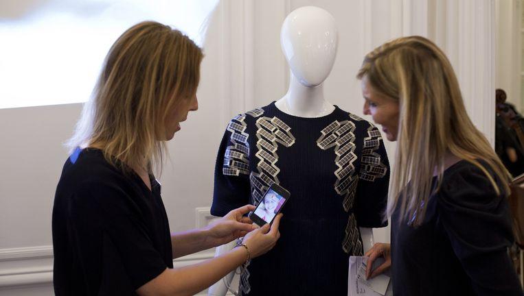 Ontwerpster Pauline van Dongen (links) donderdag op de opening van het Atelier Néerlandais. Ze maakte een trui met zonnecellen die een mobiele telefoon kunnen opladen. Beeld Bart Koetsier