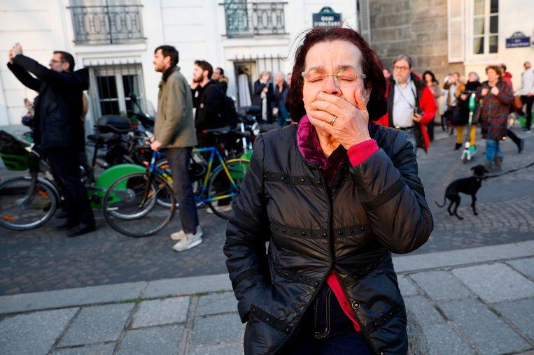 Een vrouw kijkt toe hoe de vlammen uit de Notre-Dame slaan.