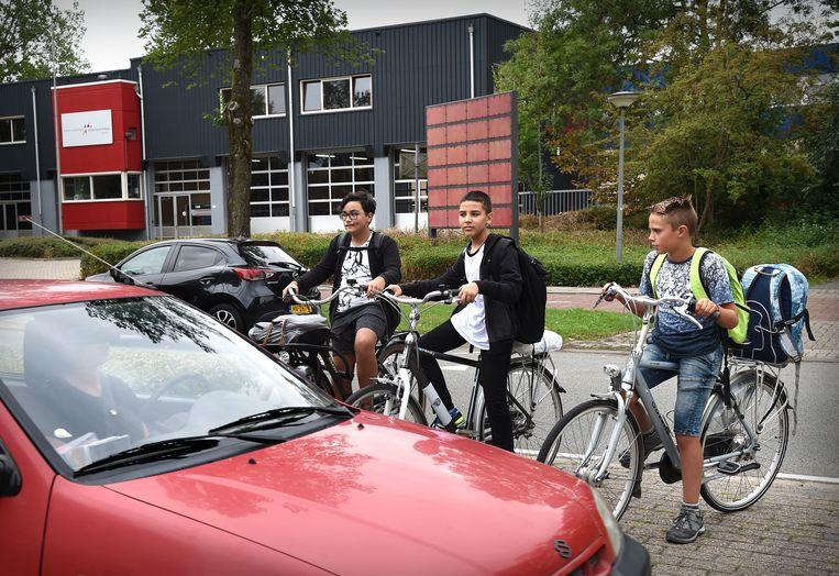 Brugklassers in Arnhem hebben zojuist hun boeken gehaald en proberen de weg voor hun school over te steken. Beeld Marcel van den Bergh
