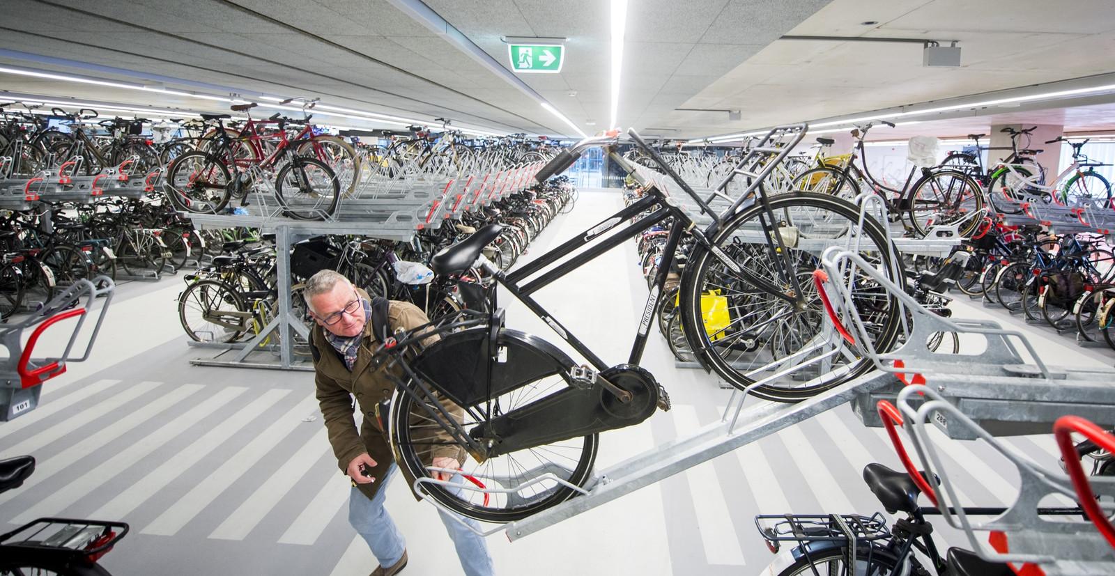 Een man pakt zijn fiets uit de stalling van station Delft.