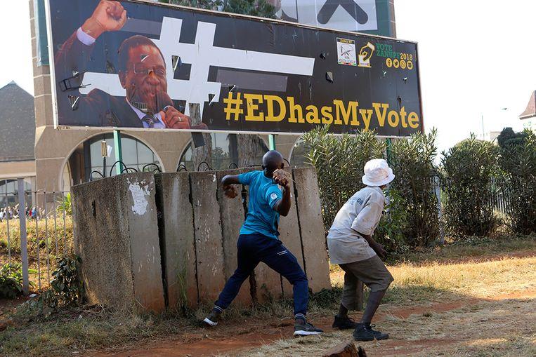 Jongens gooien stenen naar een verkiezingsposter van president Emmerson Mnangagwa. Beeld AP