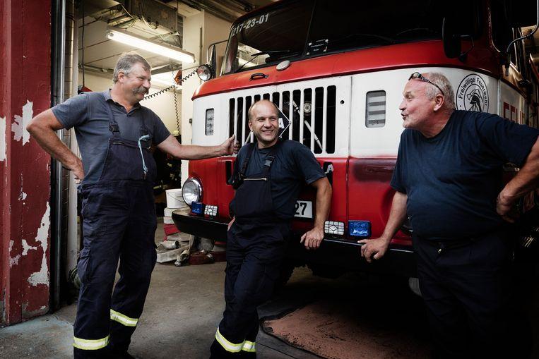 Leden van de vrijwillige brandweer voor de enige brandweerwagen van Tröglitz. Vanaf links Thomas Walther, Marco Schmeisser en nestor Reiner Seifert, die het de brandstichters vooral kwalijk neemt dat ze de levens van de buren hebben geriskeerd. Beeld Daniel Rosenthal