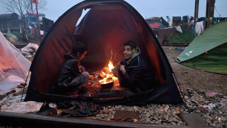 Kinderen hebben in een tent een vuurtje gemaakt in een geïmproviseerd vluchtelingenkamp bij de Griekse plaats Idomeni, op de grens met Macedonië. Beeld null