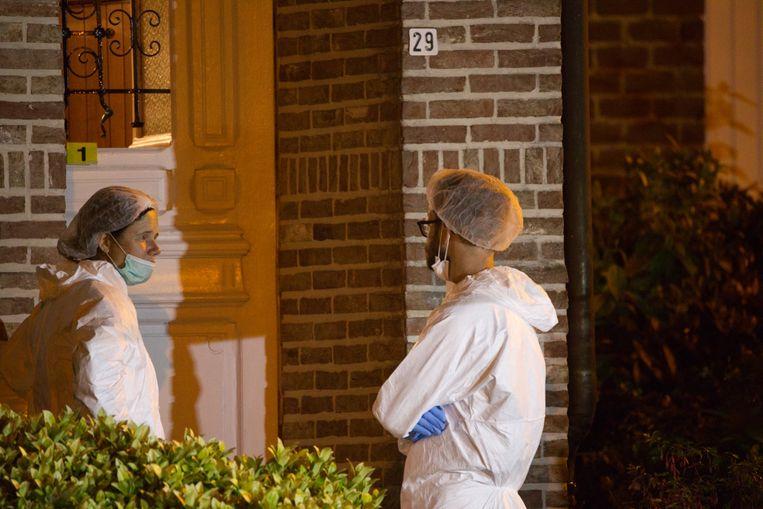 Mensen van het labo onderzoeken de bloedsporen op de deur.