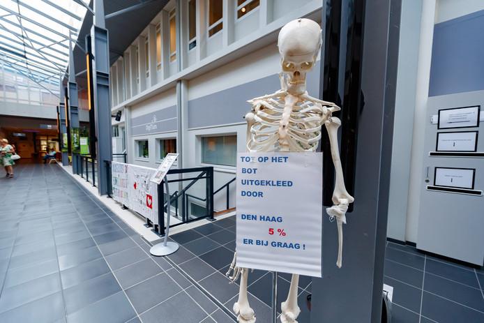 Een skelet als symbool voor ziekenhuispersoneel dat 'tot op het bot is uitgekleed'.
