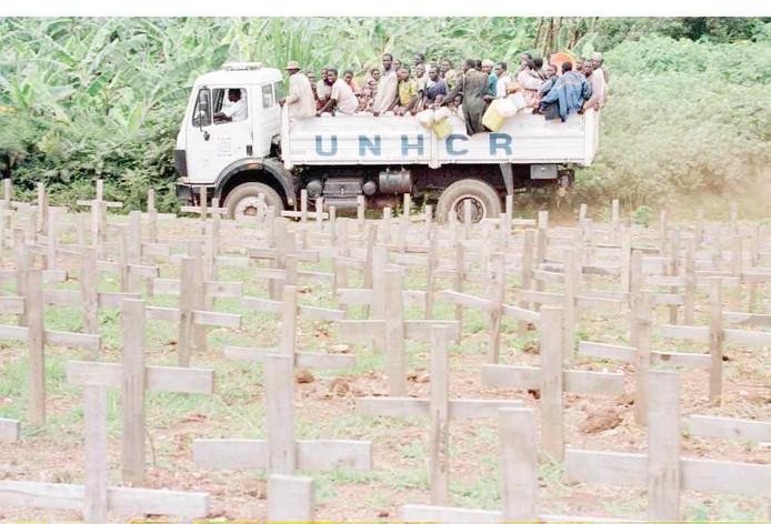Een VN-vrachtwagen met Rwandese vluchtelingen passeert in november 1994 een kerkhof met graven van vermoorde Tutsi's. Veel van de moordenaars dronken het Primus-bier van Heineken's lokale dochteronderonderneming.