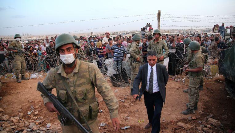 Turkse soldaten bewaken Syrische vluchtelingen die net de grens zijn overgestoken op de vlucht voor het geweld van IS. Beeld getty