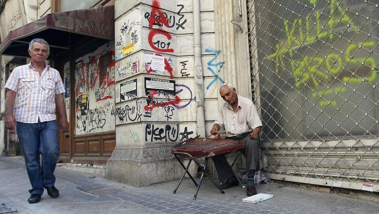 Griekse straatmuzikant zit voor gesloten winkel. Beeld ANP