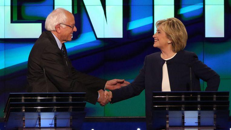 Hillary Clinton (R) en Bernie Sanders - beide presidentskandidaat voor de Democraten - schudden elkaar de hand tijdens een debat in Las Vegas. Beeld afp