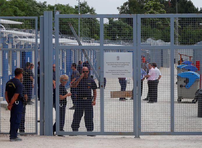 Bewakers staan bij de poort van de transitzone in Tompa, waar migranten worden opgevangen in containerkampen en hun asielaanvragen worden verwerkt.