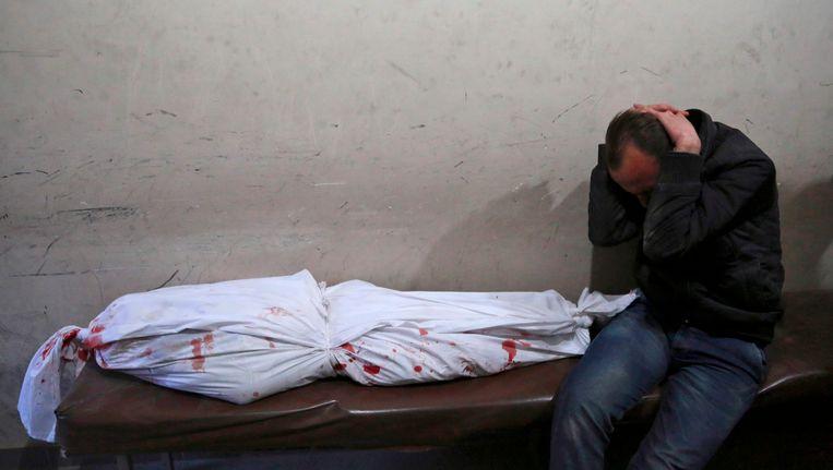 Een man rouwt om het verlies van een dierbare na bombardementen op een ziekenhuis in Oost-Ghouta, afgelopen maandag. Beeld afp