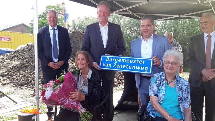 Gerard Hoiting (directeur wegenbouwer Roelofs), wethouder Ivo ten Hagen (Woerden), gedeputeerde Dennis Straat en wethouder Kees Oskam (Bodegraven-Reeuwijk) flankeren Antoinette van Zwieten (links) en haar zus na de onthulling van het straatnaambord van de randweg.