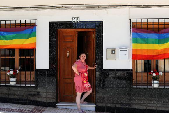 Een vrouw poseert bij enkele regenboogvlaggen voor haar huis.